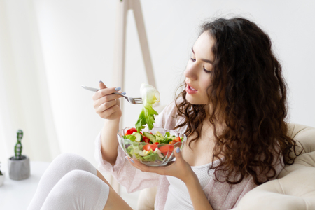 Young girl woman female wear pajams sleepwear, white top and stockings sitting on sofa and eating getting breakfast green healthy salad in interior light room. Morning route concept