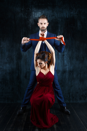 Couple in dating. Rich man male dress skirt tying woman hands. Woman female in expensive red evening dress with tied hands by red tie on dark background. Henpecked sexual issues relationship concept.