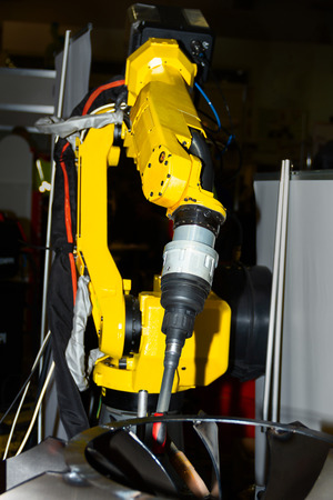 Yellow welding plasma kuka robot hand using in heavy industry for manufacturing, engineer processing or assemblies metal parts of machines