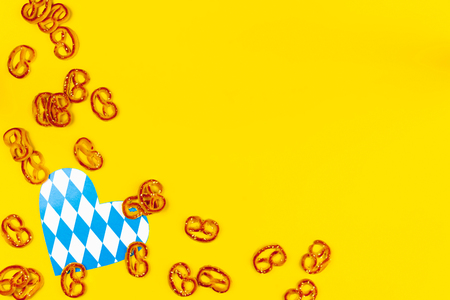 October fest concept. Sweet tasty wheat breads pretzels as snack appetizer to beer with blue decorative heart love on yellow background.  Ads event of october beer festival in autumn october month Stock Photo