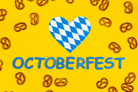 October fest concept. Wheat tasty sweet snacks pretezels, heart love in blue white and blue wooden text