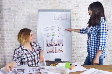 Young freelancers interior designers working develop new appartment project in design studio. Two women girl female meeting with meet desk with pin up sketches drawings and drafts of new project Stock Photo