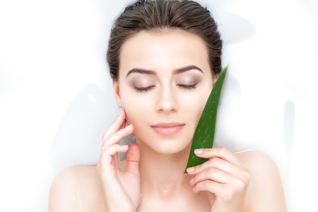Portrait of young female woman adult with clean pure skin taking spa smiling relaxing in bath with aloe white soap shampoo water. Skin beauty health care concept. Body part shoulder