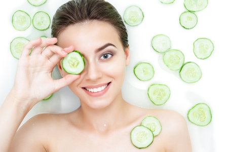 Portrait of beauty caucasian female woman with clean pure skin taking spa relaxing in bath with cucumber slices white soap shampoo water. Skin beauty health care concept. Body part shoulder