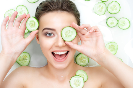 Portrait of beauty caucasian female woman with clean pure skin taking spa relaxing in bath with cucumber slices white soap shampoo water. Skin beauty health care concept. Body part shoulder Reklamní fotografie