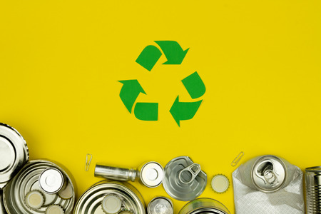 Green recycle reuse sign symbol with metal aluminium cans, covers, jars on yellow background. Eco ecology environment issue  care garbage recycling reuse, safe planet, ecology concept