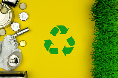 Environment issue  care, recycling and garbage trash concept. Metal aluminium cans jars lying with green nature grass with green recycling symbol on yellow background. Safe planet concept.