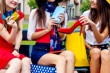 Happy colorful women females adults girls friends in hats and colorful dresses sitting outdoor after shopping in shopping mall. Admired by new red high heels. Shop sales, black friday concept