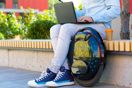 Modern young adult male man student freelancer entrepreneur software engineer with black laptop and futuristic ecological electric unicycle wears casual cloth sitting outdoor park working studying