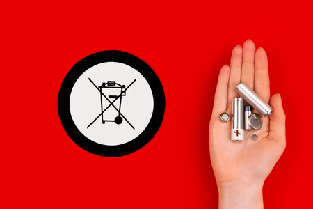 Environmentally friendly world / recycling green energy concept. Old used batteries isolated on red background and trash bin symbol as