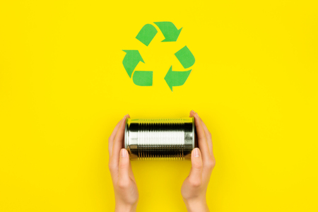 Human hands with metal aluminium can jar on yellow background with green recycle reuse arrow sign symbol. Eco ecology environment issue / care garbage recycling reuse, safe planet, ecology concept