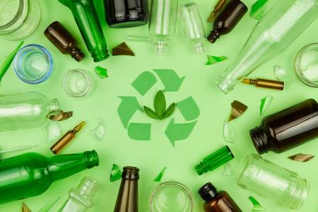 Simbolo verde del segno di riciclo con la bottiglia, le pillole ed i tubi di vetro dell'immondizia della spazzatura su fondo isolato verde. Riciclo ecologico, problema ambientale, pianeta sicuro, concetto di riutilizzo dei rifiuti riciclati
