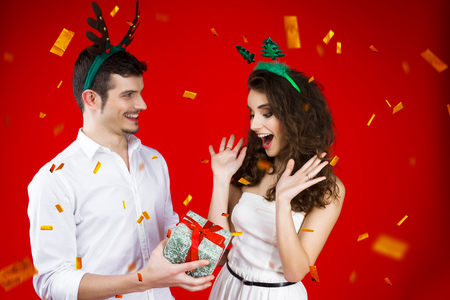 New Year party concept happy fun smiling friends couple wearing fairy tale carnival costume deer Christmas tree hat give present surprise celebrating winter holidays isolated red background confetti