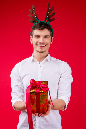 New Year party concept happy fun smiling charming handsome hipster man guy male celebrating winter Christmas holidays wearing white shirts deer horn hat holding give presents box gift red background Stock Photo