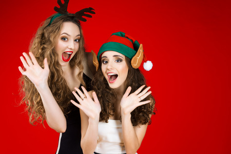 happy smiling young beautiful women female adult wearing fairy tale green Christmas elf hat ears deer horns little black white dress celebrating winter holidays new year party isolated red background