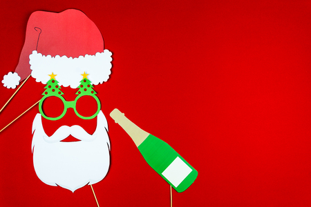 Flat designed funny Santa with red Santa's hat,  beard and hipster pine tree glasses with champagne as holiday party props isolated on red background. Merry Christmas and Happy New 2019 Year concept.