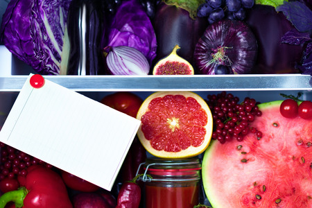 Fresh organic healthy raw antioxidant violet, red, food, vegetables, fruits and juices in vegan vegetarian fridge: fig,  watermelon, cabbage, onion, pepper, eggplant, tomato juice and space for text. Stock Photo
