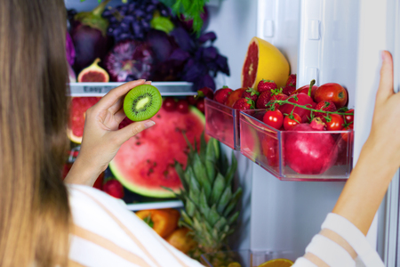 Vegan vegetarian woman female taking green healthy antioxidant kiwi for eating after market near fridge with colorful veggies, raw juice and fruits: grapefruit, tomatoes, watermelon, pineapple, fig