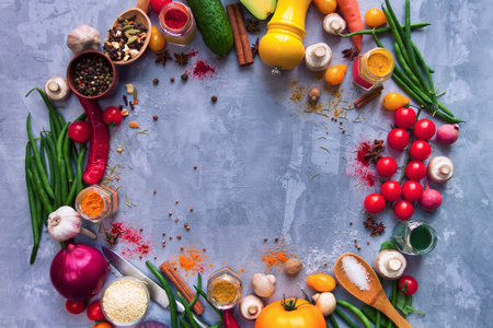Circle of healthy colorful spicy flavoured seasoning with fresh summer organic antioxidant fruits and vegetables for vegan or vegetarian recipes isolated on grey background. Healthy lifestyle concept Stock Photo