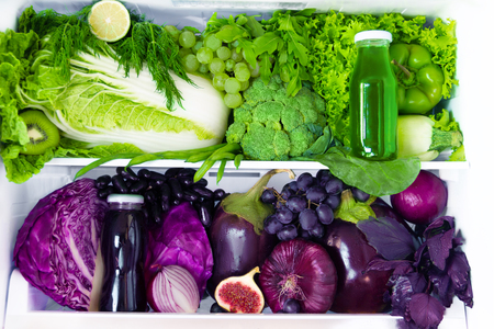Summer fresh organic healthy raw antioxidant green and violet food, vegetables, fruits and juices in vegan vegetarian in opened full fridge of vitamins. Healthy eating, diet and lifestyle concept. Stock Photo