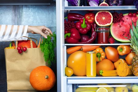 Vegan vegetarian woman female hand putting paper package of vegetables greens after market near fridge with colorful veggies, raw juice and fruits: red pepper, oranges, carrots, watermelon, pineapple Stock Photo