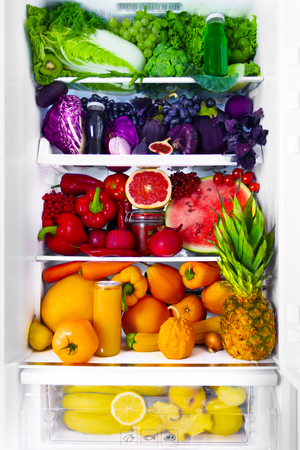 Fresh organic healthy raw antioxidant violet, red, green, orange and yellow food, vegetables, fruits and juices in vegan vegetarian opened full fridge of vitamins. Healthy eating diet and lifestyle.