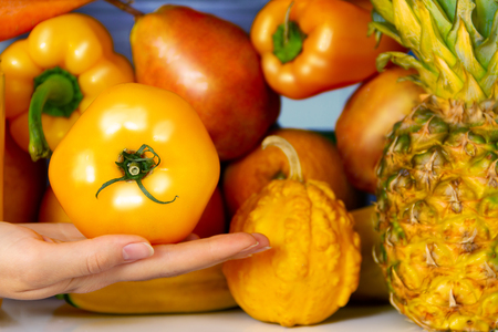 Summer yellow healthy organic antioxidant tomato, veggies vegetables and fruits: pepper, pumpkin, pear orange as symbol of healthy eating, diet and lifestyle. Fridge, vegan. vegetarian and raw concept Stock Photo