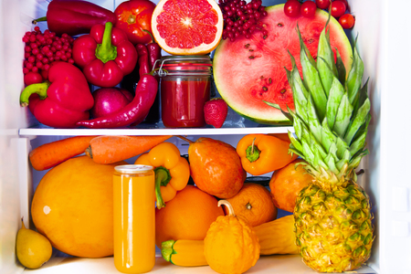 Summer fresh organic healthy raw antioxidant red and orange food, vegetables, fruits and juices in vegan vegetarian in opened full fridge of vitamins. Healthy eating, diet and lifestyle concept. Stock Photo