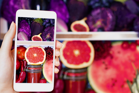 Vegan vegetarian woman female taking picture of healthy antioxidant colorful food, veggies, raw juice and fruits for eating in fridge: grapefruit, tomatoes, watermelon, fig and onion by smartphone Stock Photo