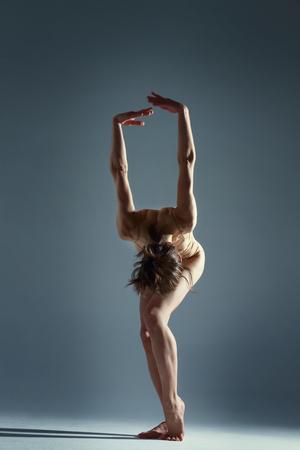 Muscle brunette beauty female girl adult woman dancer athlete gymnast wearing beige dance clothing bodysuit making dance element performance on isolated grey  black background scene
