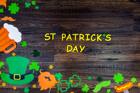 Saint Patrick Day concept. Paper Patrick day leprechaun props: green leprechaun hat orange beard orange mustache and lucky clover trefoil as symbol of Ireland traditional holiday on wooden background