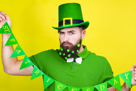 Happy young adult man male in green shirt, green leprechaun hat and tie bow with lucky clover trefoil in beard as symbol of Ireland traditional holiday Saint Patrick Day on yellow isolated  background Stok Fotoğraf - 115936319