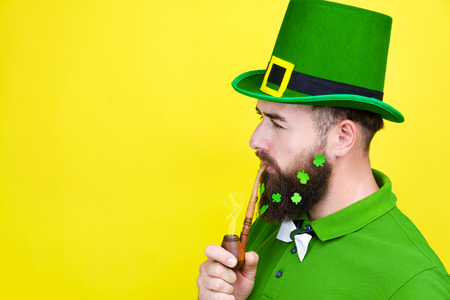 Happy young adult man male in green shirt, green leprechaun hat and tie bow with lucky clover trefoil in beard as symbol of Ireland traditional holiday Saint Patrick Day on yellow isolated  background Stok Fotoğraf