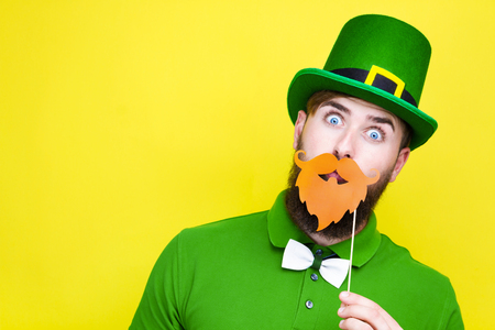 Happy young adult man male in green shirt, green leprechaun hat and tie bow with orange beard props on beard as symbol of Ireland traditional holiday Saint Patrick Day on yellow isolated  background