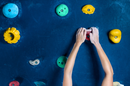 Hands of successful happy muscle healthy winner climber mountaineer alpinist female woman climbing training in climbing wall in bouldering competition. Success healthy lifestyle do not give up concept