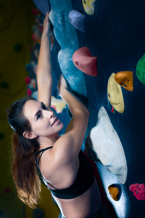 Successful strong confident muscle woman female alpinist climber climbing  to dreams goals, get healthy lifestyle. Training to achieve victory in competition in climbing wall, rock climbing bouldering