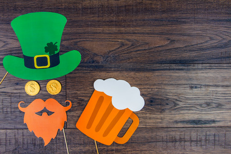 Saint Patrick Day concept. Paper Patrick day leprechaun props: green leprechaun hat, orange beard,orange mustache and lucky clover trefoil as symbol of Ireland traditional holiday with glass of beer Stockfoto