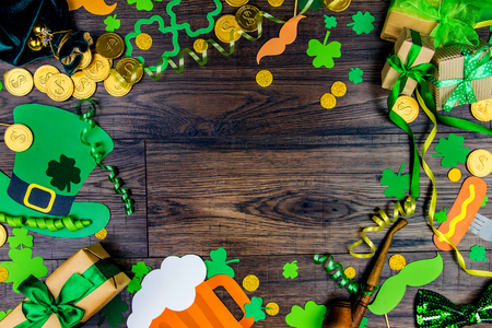 Saint Patrick Day concept. Paper Patrick day leprechaun props: green leprechaun hat gold coins, orange mustache and lucky clover trefoil as symbol of Ireland traditional holiday on wooden background