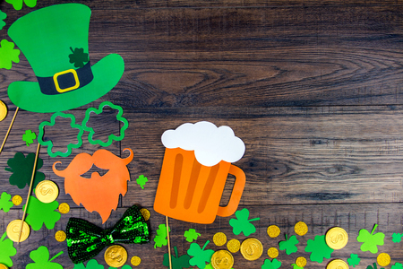 Saint Patrick Day concept. Paper Patrick day leprechaun props: green leprechaun hat orange beard glass of beer and lucky clover trefoil as symbol of Ireland traditional holiday on wooden background