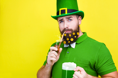 Happy young adult man male in green shirt, green leprechaun hat and tie bow with gold coins in beard and smoking pipe as symbol of Ireland traditional holiday Saint Patrick Day on isolated  background