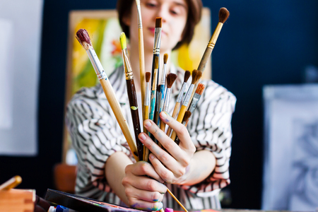 Young beautiful artist teacher student woman girl boy in art workshop studio surrounded by colorful black white painting hold huge bunch stack of art brushes for oil acrylic paints wear striped robe