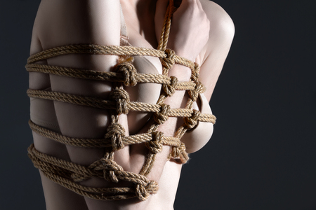 Closeup chest of young woman are tied with hand with beautiful knots with natural ropes on gray background. Ancient Japanese art of aesthetic bandage and tying shibari kinbaku. Sexual games concept.