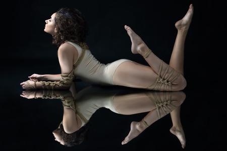 Submission slave woman bound in fashion style rope shibari kinbaku Japanese knot lie on floor with symmetry reflection Bdsm mistress dominant punishment sadism masochism concept.