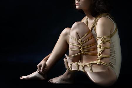 Submission slave woman bound in fashion art style rope shibari kinbaku Japanese knot. Bdsm mistress master dominant punishment flogging sadism masochism concept.