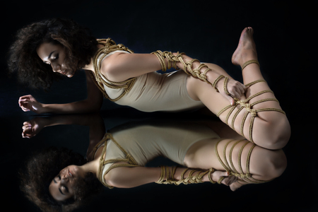 Submission slave woman bound in fashion style rope shibari kinbaku Japanese knot lie on floor with symmetry reflection Bdsm mistress dominant punishment sadism masochism concept.