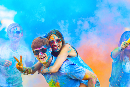 Couple in sunglasses soiled with colorful bright paints, are posing and smiling. Man holding woman on his shoulders. Company of young people friends having fun with holi paints. Holi party concept.