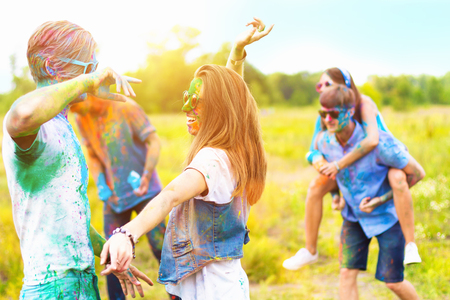 Happy positive smiling fun friends wearing sunglasses all stained with colorful paint celebrating dance laughs on Holi festival party On color dust smoke powder cloud background in park field outdoor