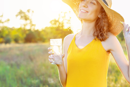 Happy beauty young woman female with pure glass of water wears yellow lite dress and summer hat smiling walking outdoor in green park at sunny warm light day. Active outdoor lifestyle leisure concept.
