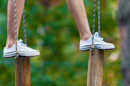 Closeup of female slender legs in white sneakers keep balance on wooden stumps hanging on ropes on trees in park. Rope park with obstacles and ziplines. Extreme rest and summer activities concept.
