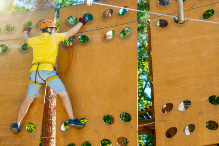 Young male man adult wears protective helmet with action camera having fun in extreme rope park, amusement park. Climbing in wooden wall at green forest. Active healthy lifestyle in spring or summer. 写真素材